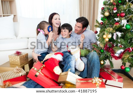 Happy family playing with Christmas gifts at home