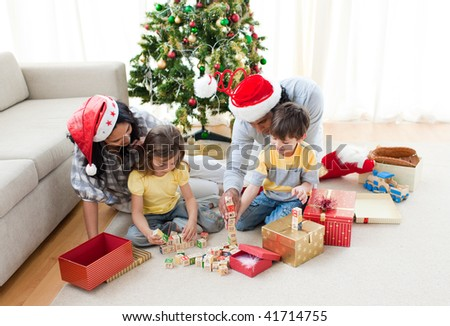 Happy family playing with Christmas presents  at home