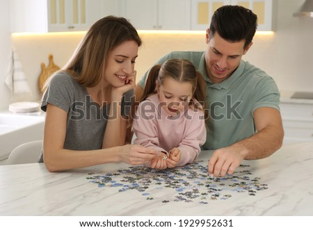 Happy family playing with puzzles at home