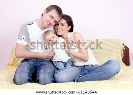 Happy family plays in the bed
