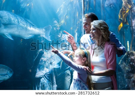 Shutterstock Happy family pointing a fish in the tank at the aquarium