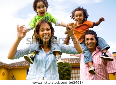 happy family portrait having fun outdoors at their home