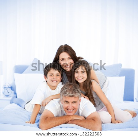 Happy family portrait in bed with two parents and brother sister