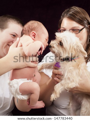 Happy family portrait in the studio. Two mothers, newborn and dog.
