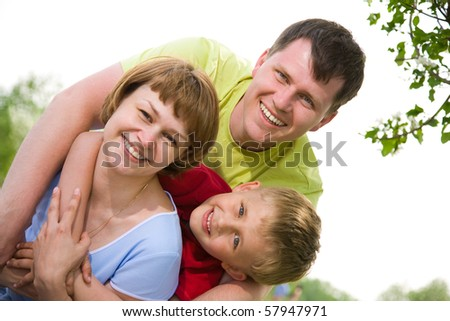 happy family portrait of attractive couple with their young son background on the blue sky