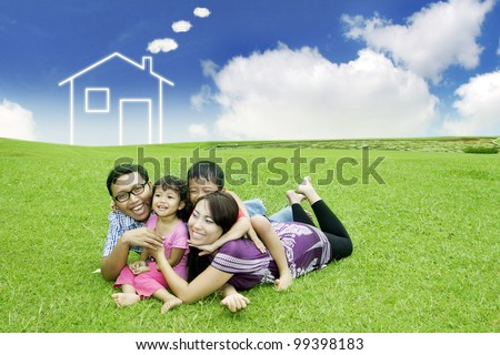 Happy family  posing on field with a drawn house in background