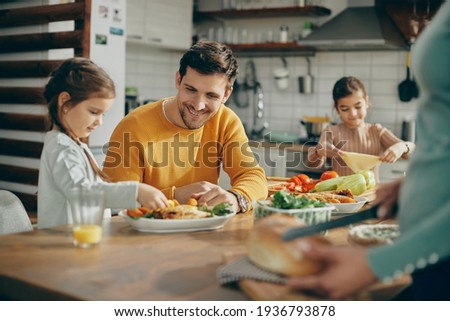 Happy family preparing dining table for lunch at home. Focus is on father.