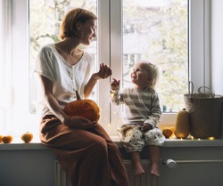 Happy family preparing for Halloween at home together. Mother and her little daughter sitting near window with carving pumpkin head jack lantern. Autumn mood