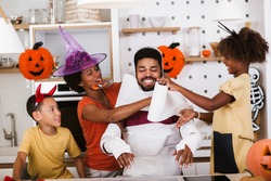 Happy family preparing for Halloween, having fun.