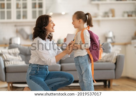 Happy family preparing for school. Little girl with mother. Foto stock ©