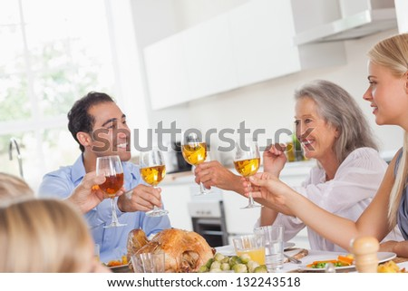 Happy family raising their glasses at thanksgiving dinner