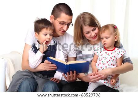 Happy family reading a book on sofa - stock photo