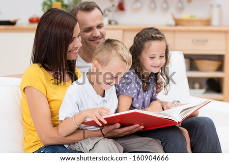 Happy family reading a book together with attractive young parents grouped with their two small children on a couch in the living room - stock photo