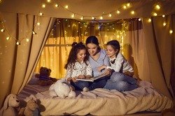 Happy family reading good book in the evening. Young mother telling bedtime stories to little children. Mommy and daughters enjoying fairy tales sitting in cozy playroom tent decorated with LED lights