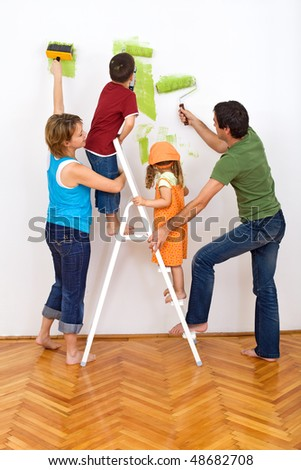 Happy family redecorating the house - painting the wall