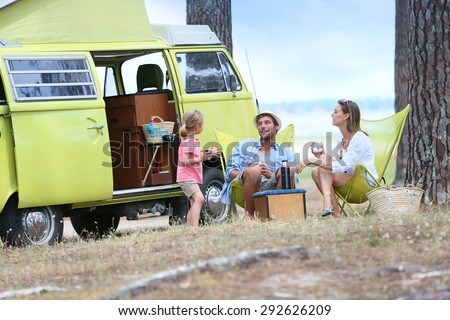 happy family relaxing by camper ...