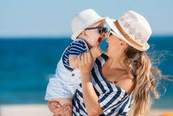 Happy family relaxing by the sea. Happy family resting at beach in summer. mother with baby boy resting on the beach. Young mother and her adorable little daughter on beach vacation
