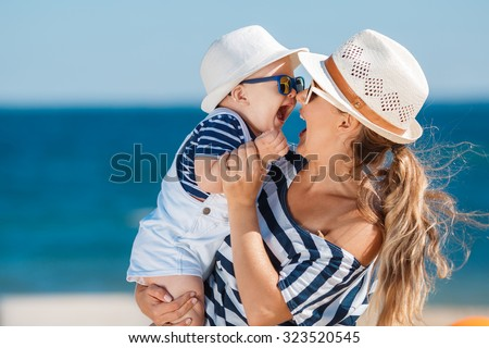 Happy family relaxing by the sea. Happy family resting at beach in summer. mother with baby boy resting on the beach. Young mother and her adorable little daughter on beach vacation #323520545