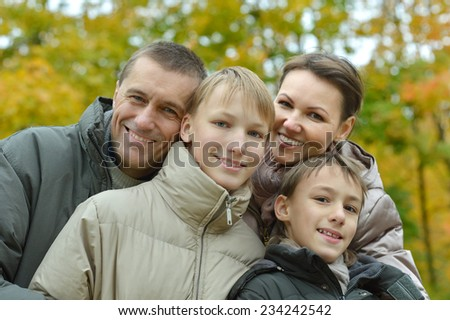 Happy family relaxing in autumn park together #234242542
