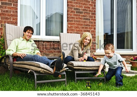 Happy family relaxing in backyard of new home with toddler