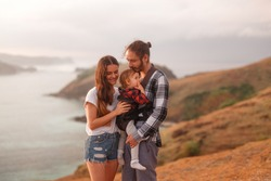 Happy  family relaxing on beach holiday, stand on sea cliff with little baby