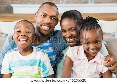 Happy family relaxing on the couch in living room #345235520