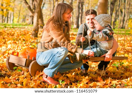 Happy family relaxing outdoors In autumn park