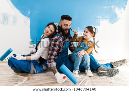 Happy family renovating their home. They are painting a wall together.