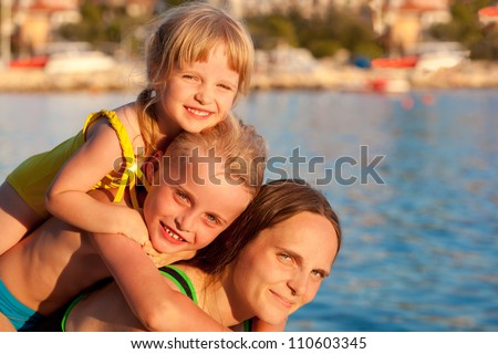 Happy family resting by sea in summer