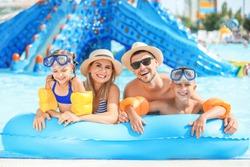 Happy family resting in aqua park