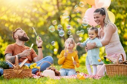 Happy family resting in summer park.Cheerful family picnicking in the park.Summertime and vacation concept.