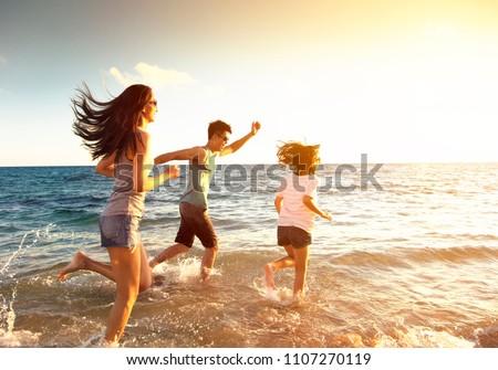 happy family running on the beach #1107270119