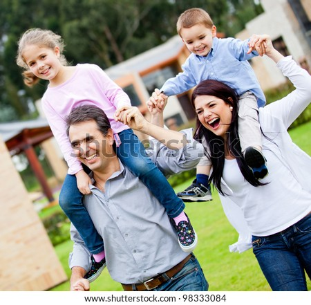 Happy family running outdoors and parents carrying kids