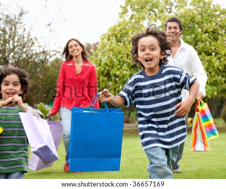 Happy family running outdoors with shopping bags