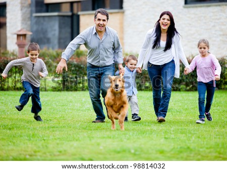 Happy family running with their dog outdoors - stock photo