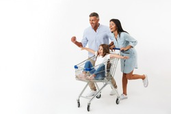 Happy family runnnig while shopping together with a supermarket trolley, little daughter sitting in a trolley isolated