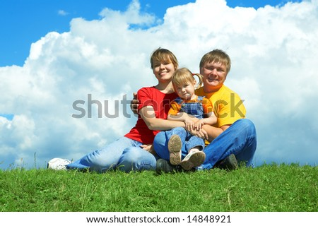 happy family sit on green grass under sky with clouds