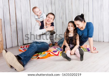 Happy family sit with toys on colorful blanket on the floor. Boy sits on the father`s shoulders. Indoor photo shot