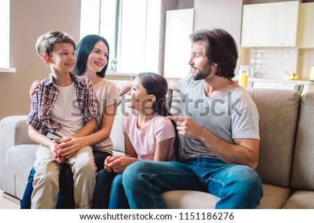 Happy family sits together on sofa. Boy is on mother's lap. Girl sits between woman and man. They are looking at each other.