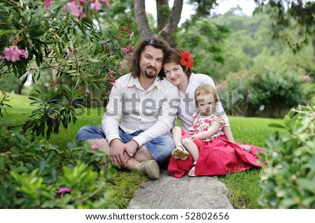 Happy family sitting in a tropical scenery