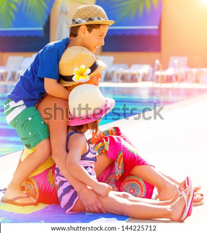 Happy family sitting near poolside, mother with two cute kids enjoying summer holidays, little sister and brother with young mom on luxury resort, love concept - stock photo
