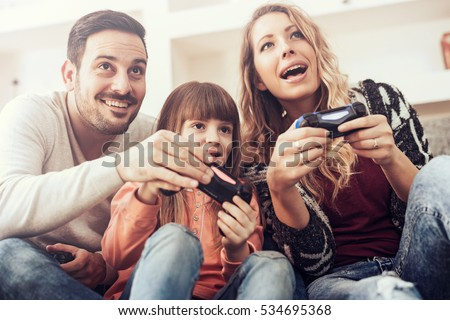 Happy family sitting on a sofa and playing video games.