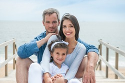 happy family sitting on a wooden pontoon in front of the sea