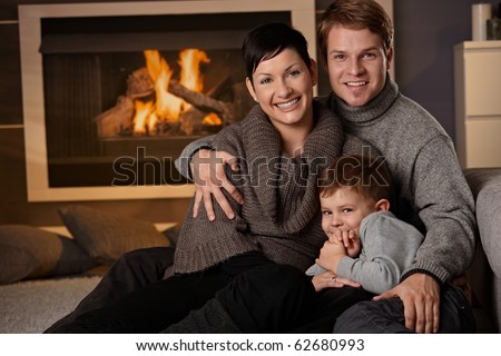 Happy family sitting on couch at home in a cold winter day, looking at camera, smiling.