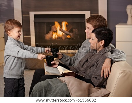 Happy family sitting on couch at home in front of fireplace, drinking tea, smiling.