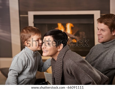 Happy family sitting on couch at home in front of fireplace, looking at camera, smiling.?