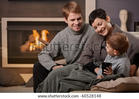 Happy family sitting on couch at home in front of fireplace, smiling.