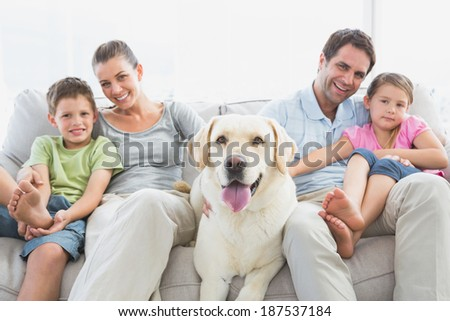 Happy family sitting on couch with their pet labrador at home in the living room
