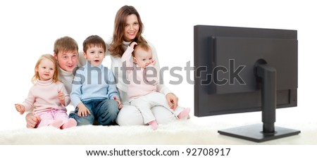 happy family sitting on floor and watching TV or monitor with great interest - stock photo