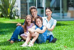 happy family sitting on grass in front of house, parents with two children smile